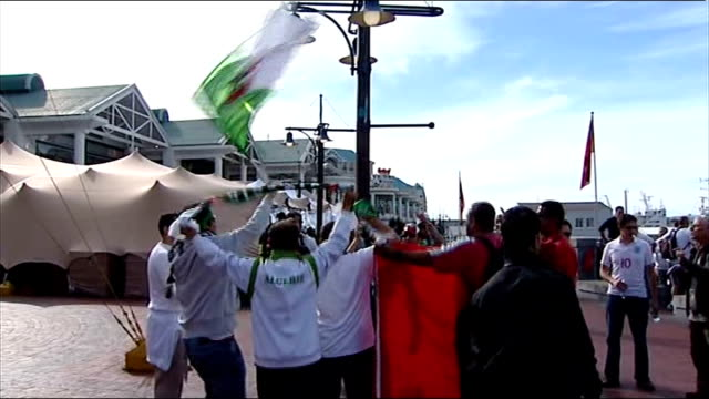 build up to england v algeria ext algerian fans singing and waving flags vox pops - 2010 stock videos & royalty-free footage