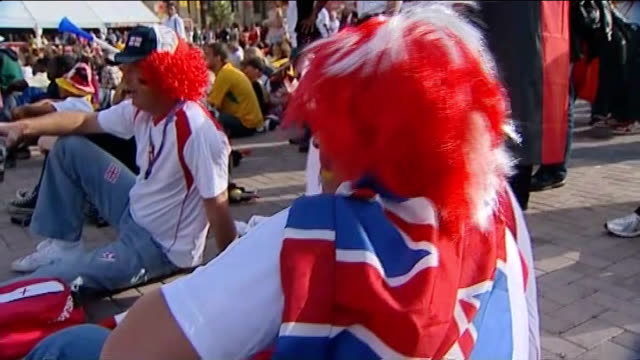 build up to england v algeria football fans with silly wigs one with union jack flag draped around shoulders and german flag painted on face germany... - body adornment stock videos and b-roll footage