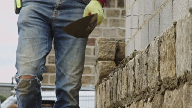 builder adding mortar to wall - costruire video stock e b–roll