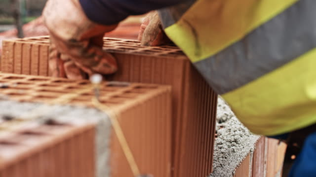 byggare bygga en vägg av ihåliga tegelstenar - tegelsten bildbanksvideor och videomaterial från bakom kulisserna