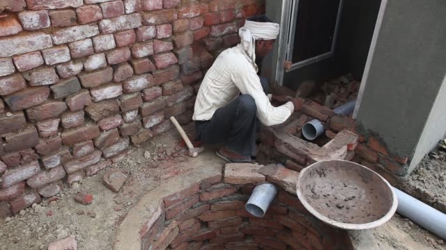 a builder constructs a toilet block one of the first in the village and built with assistance from sulabh international social service organisation... - haryana stock videos & royalty-free footage