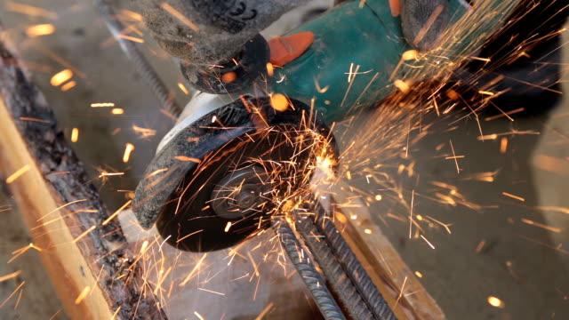 Builder cuts steel bars.