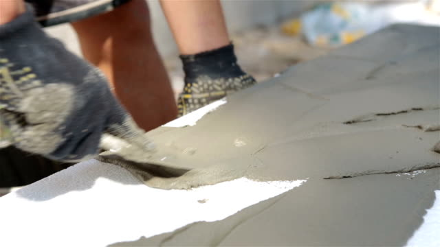 Builder inflicts of construction glue on polystyrene.