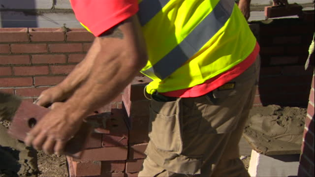 builder laying bricks on construction site in haworth nottinghamshire - brick stock videos & royalty-free footage