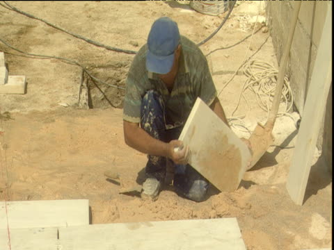 builder lays marble slab on bed of sand hits with hammer to flatten and level during reconstruction of panathinaikon stadium for the 2004 olympics... - panathinaiko stadium stock videos & royalty-free footage