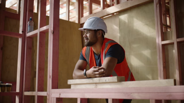 Builder on construction site leaning on timber framing