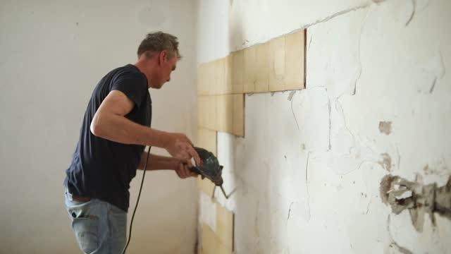 vidéos et rushes de constructeur enlevant les vieux carreaux de la salle de bain. marteau de démolition. - un seul homme d'âge moyen