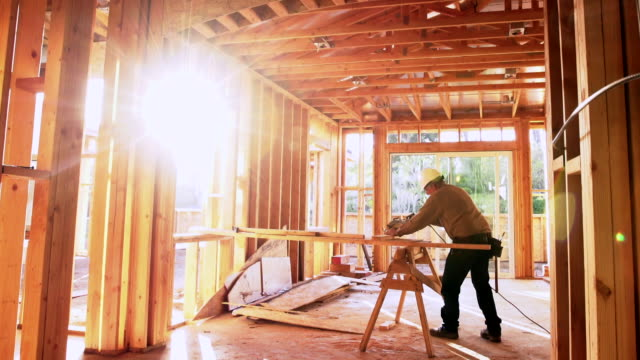 WS TS Builder sawing wood in a building site