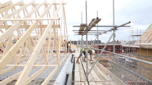 a builder uses a nail gun on timber roof structure of a house during construction at a persimmon plc residential housing site in rainham uk on friday... - plc stock videos & royalty-free footage