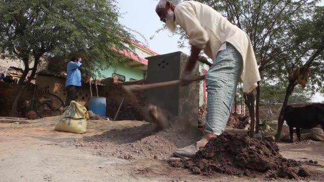a builder uses a trowel to mix concrete in a bowl during construction of a toilet block one of the first in the village and built with assistance... - haryana stock videos & royalty-free footage