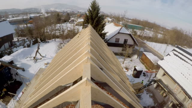 pov builder walking across a wooden beam on the roof of the house - roof beam stock videos & royalty-free footage