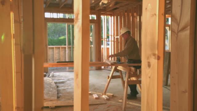 vídeos de stock, filmes e b-roll de ws ts builder working in a construction site - serra elétrica