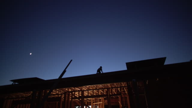 ws builder working on the roof of a house at night - hammer stock videos and b-roll footage