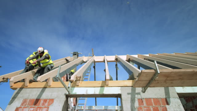 ld builders attaching the wooden beams on the roof in sunshine - construction material stock videos & royalty-free footage