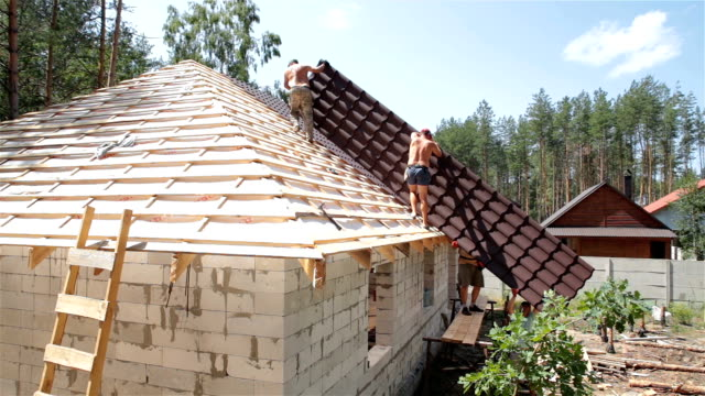 builders build a roof. - roof tile stock videos & royalty-free footage