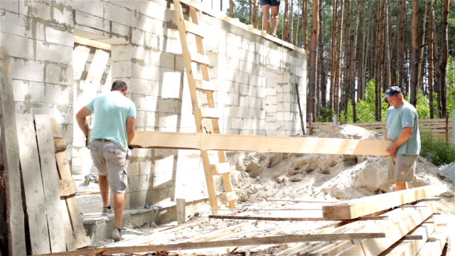 builders carry a wooden beam into the house. - roof beam stock videos & royalty-free footage
