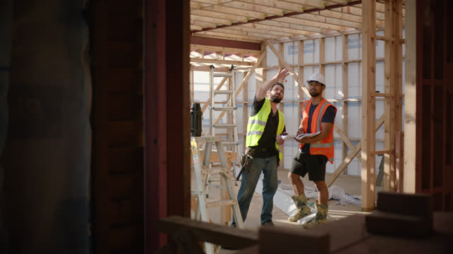 builders discuss plans and building project - foreman stock videos & royalty-free footage