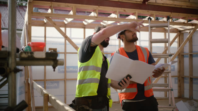 builders discuss plans of building project - foreman stock videos & royalty-free footage