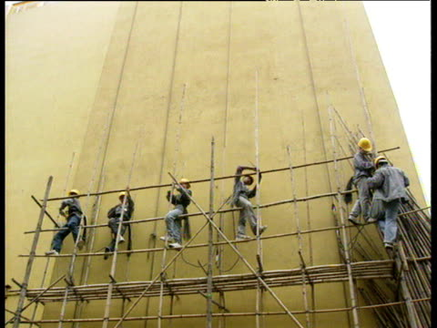 builders erecting bamboo scaffolding against wall of building hong kong - scaffolding stock videos & royalty-free footage