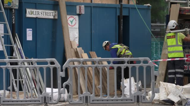 builders get back to work on a site in east london after the prime minister announced the general contours of a phased exit from the current lockdown... - pavement stock videos & royalty-free footage
