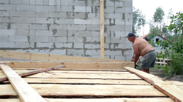 builders lift the wooden beam to the roof. - roof beam stock videos & royalty-free footage