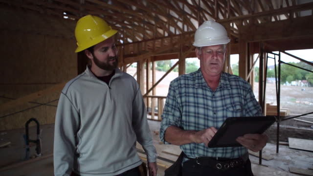 ms ts builders looking at a digital tablet at a building site - contractor stock videos and b-roll footage