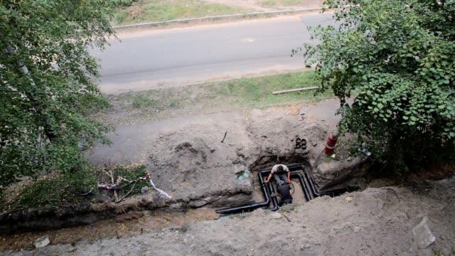 bauherren machen die isolierung der neuen pipeline. - rohr stock-videos und b-roll-filmmaterial