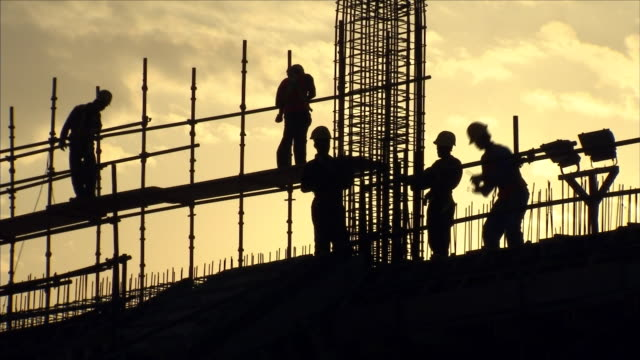 builders on construction site at sunset - balkengerüst stock-videos und b-roll-filmmaterial