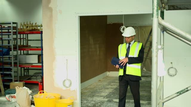 vidéos et rushes de builders on construction site - un seul homme d'âge moyen