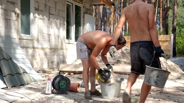 Builders prepare a construction glue in the bucket.