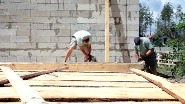 builders prepare a wooden beam for the construction of the roof. - roof beam stock videos & royalty-free footage