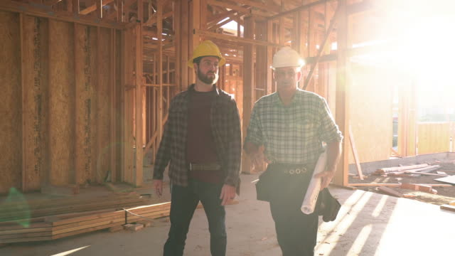 ws ts builders walking through a house under conctruction - bauarbeiter stock-videos und b-roll-filmmaterial