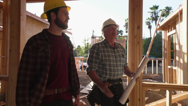 ms ts builders walking through a house under construction - construction worker stock videos & royalty-free footage