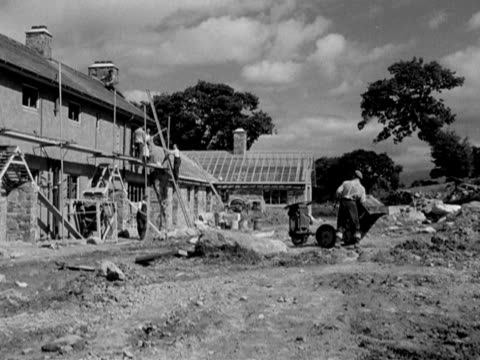 Builders work on renovating farm cottages in the Welsh countryside