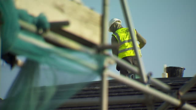 builders working on housing building site in essex that uses migrant labour to fill jobs - residential building stock videos & royalty-free footage