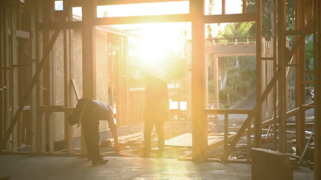 ws builders working together on a house at sunset - 建物の骨組み点の映像素材/bロール