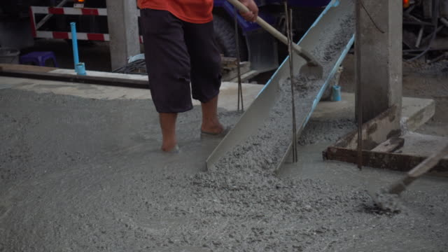 building a cottage. workers take concrete from a mixer into a wooden formwork - cement mixer stock videos and b-roll footage