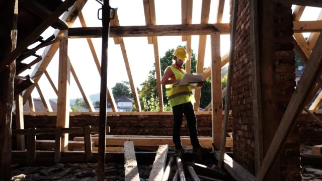 building a house roof. a confident female architect working on the roof structure on a construction site of a residential building on a bright sunny day. - quality control stock videos & royalty-free footage