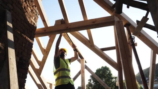 vídeos y material grabado en eventos de stock de construir un techo. un carpintero experimentado que trabaja en la construcción de un edificio residencial en un día soleado brillante. - madera material