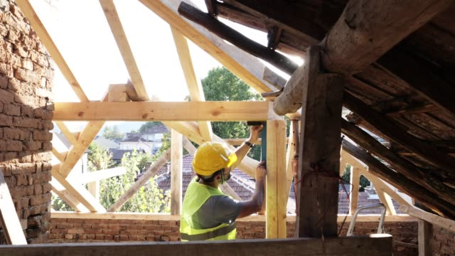 building a house roof. an experienced carpenter working at construction site of a residential building on a bright sunny day. - timber stock videos & royalty-free footage
