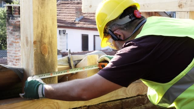 building a house roof. an experienced carpenter working at construction site of a residential building on a bright sunny day. - reflective clothing stock videos & royalty-free footage