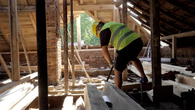 building a house roof. an experienced carpenter working at construction site of a residential building on a bright sunny day. - one mature man only stock videos & royalty-free footage