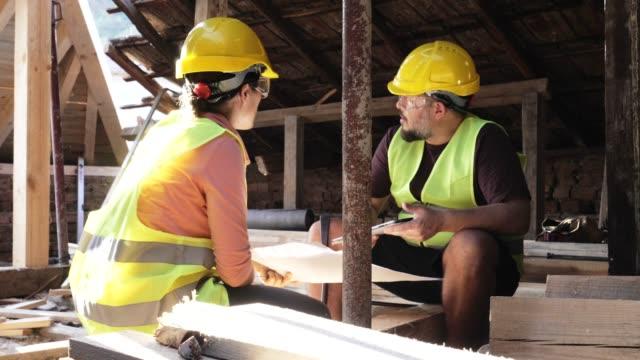 costruire un tetto di casa. incontro di un architetto donna fiducioso e di un operaio edile che discute e lavora insieme nel cantiere di un edificio residenziale in una luminosa giornata di sole. - sunny video stock e b–roll