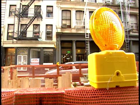 Building across barricaded street / worker pushing wheelbarrow / workers working / sidewalk by barricaded street