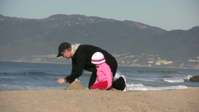 stockvideo's en b-roll-footage met (hd1080i) building, constructing sand castle on beach: mother, daughter, generations - malibu