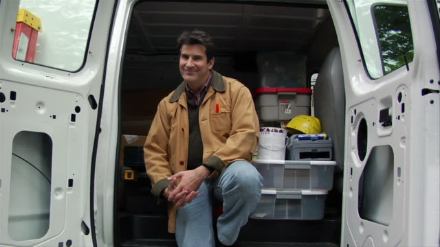 Building contractor sitting in van / smiling at camera / standing up and closing doors of van