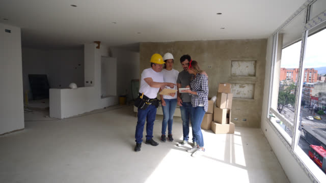 building contractors talking to happy young couple during a home renovation looking at clipboard and tablet all smiling - rebuilding stock videos & royalty-free footage