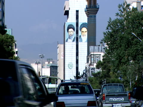 ws a building displaying two large banners while traffic drives past / tehran, iran - vox populi stock videos & royalty-free footage