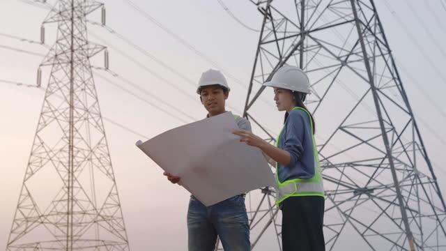 電柱の背景と話し合いながら、設計図を見ている建設現場の建築エンジニアの請負業者 - cable点の映像素材/bロール