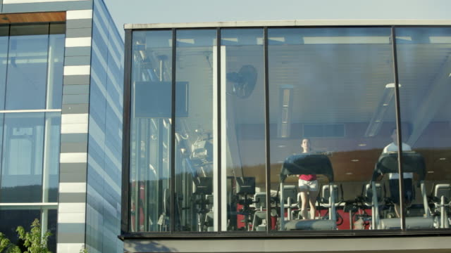 ws building exterior of gym weights room community centre, man and woman running on treadmills / vancouver, british columbia, canada - gym stock videos & royalty-free footage